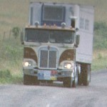 Brown cabover with trailer on the rode