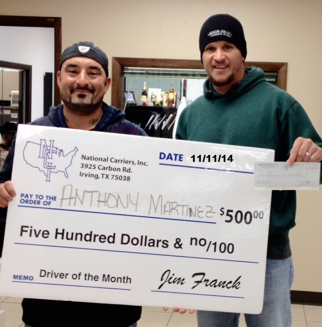 Anthony Martinez is awarded bonus check from director of Livestock Division, Jason Greer